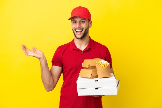 Fattorino della pizza che preleva scatole per pizza e hamburger su sfondo isolato con espressione facciale scioccata