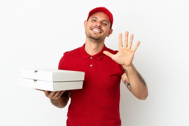 Fattorino della pizza con l'uniforme da lavoro che prende le scatole della pizza sopra il muro bianco isolato contando cinque con le dita
