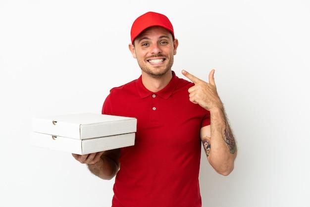 Fattorino della pizza con l'uniforme da lavoro che prende le scatole della pizza sopra la parete bianca isolata che dà un gesto di pollice in su