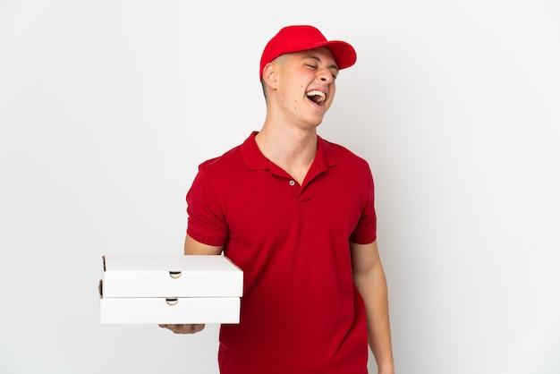 Uomo di consegna pizza con divisa da lavoro raccogliendo scatole per pizza isolato sul muro bianco ridendo
