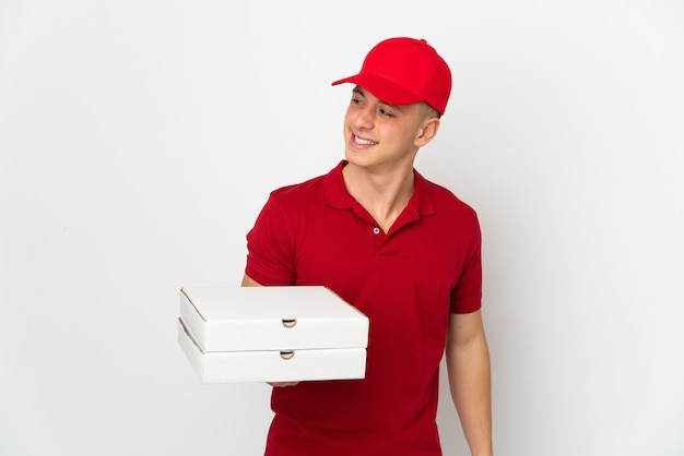 Uomo di consegna pizza con divisa da lavoro raccogliendo scatole per pizza isolato sul muro bianco che guarda al lato e sorridente