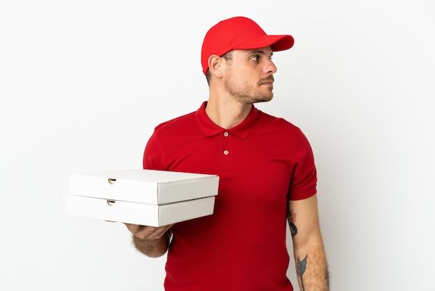 Fattorino della pizza con uniforme da lavoro che preleva scatole per pizza sul muro bianco isolato guardando di lato