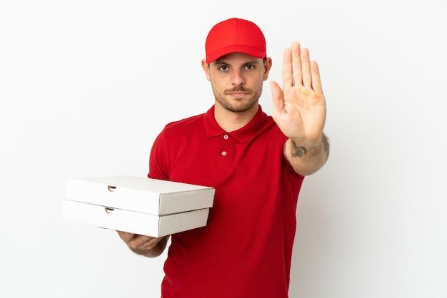 Fattorino della pizza con l'uniforme da lavoro che prende le scatole della pizza sopra la parete bianca isolata che fa il gesto di arresto stop
