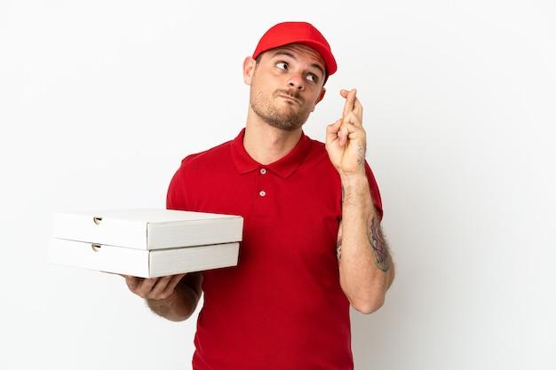 Fattorino della pizza con uniforme da lavoro che raccoglie scatole per pizza sul muro bianco isolato con le dita incrociate e augurando il meglio