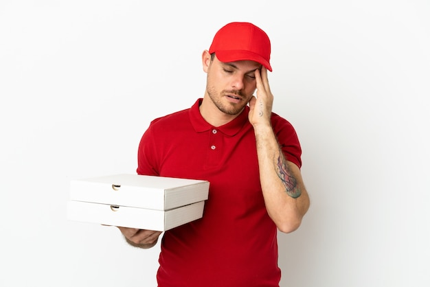 Fattorino della pizza con uniforme da lavoro che raccoglie scatole per pizza su un muro bianco isolato con mal di testa