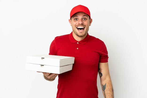 Fattorino della pizza con l'uniforme da lavoro che prende le scatole della pizza sopra la parete bianca isolata con l'espressione facciale di sorpresa