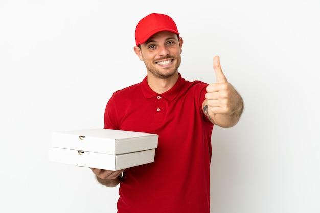Fattorino della pizza con uniforme da lavoro che raccoglie scatole per pizza sul muro bianco isolato con il pollice in alto perché è successo qualcosa di buono