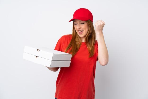 Donna di consegna della pizza che tiene una pizza sopra la parete rosa isolata che celebra una vittoria