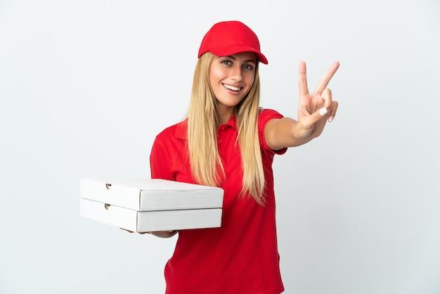 Donna di consegna della pizza che tiene una pizza isolata su fondo bianco che sorride e che mostra il segno di vittoria