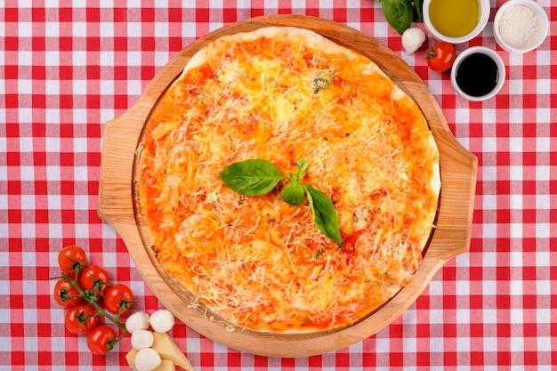 Pizza quattro formaggi con mozzarella, gongorzola, parmigiano, ricotta su una tavola di legno