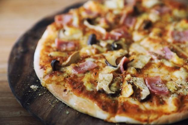 Pizza prosciutto e funghi su uno sfondo di legno