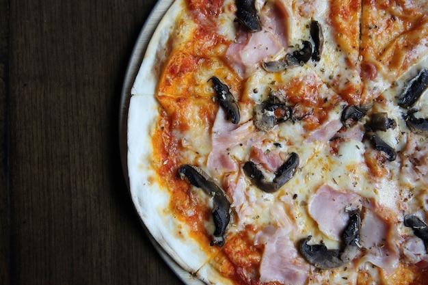 Pizza prosciutto e funghi su legno