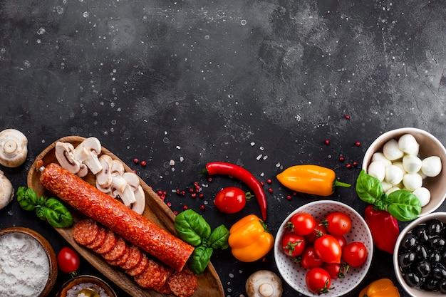 Ingredienti della pizza sullo sfondo grigio scuro. salsiccia ai peperoni, mozzarella, pomodori, olive, funghi e farina sono prodotti diversi per fare pizza e pasta