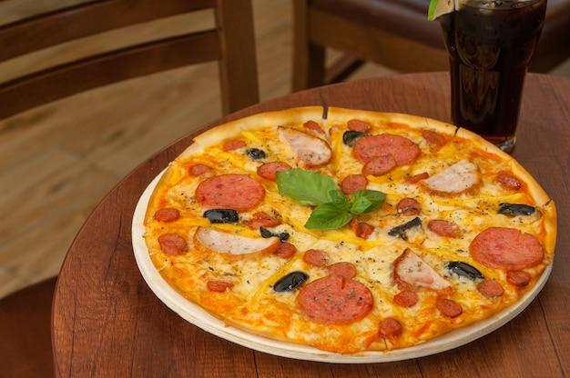 Pizza sul tavolo della cucina con una bibita fresca Foto Premium