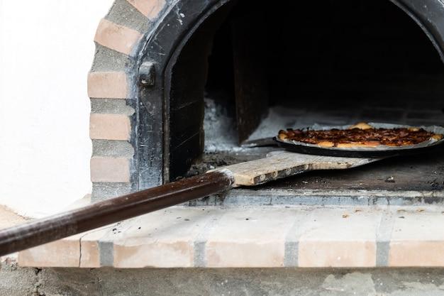 Pizza fatta in un forno a legna artigianale dipinto di bianco costruito all'esterno, sfondo