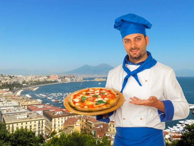 Pizzaiolo con pizza margherita a napoli.