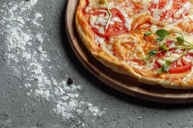Pizza margarita con pomodori, basilico e mozzarella