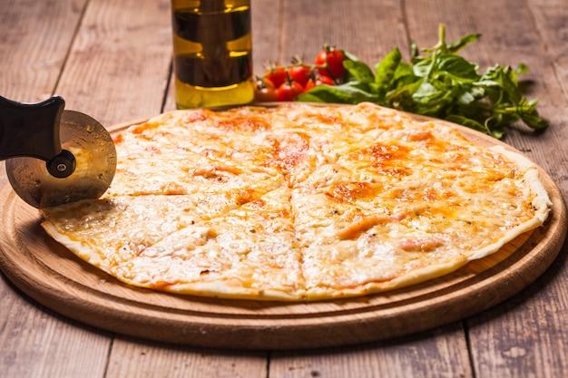 Pizza margherita su tagliere in legno e tagliapizza