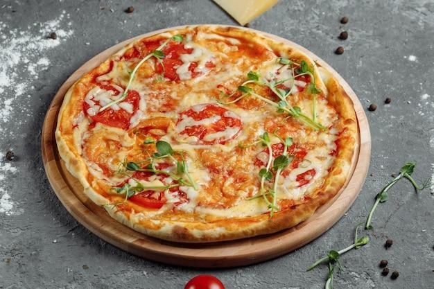 Pizza margherita su pietra nera sullo sfondo, vista dall'alto. pizza margarita con pomodoro, basilico e mozzarella close up.