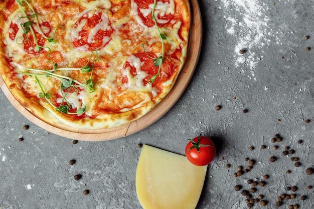 Pizza margherita su fondo di pietra nero, vista dall'alto. pizza margarita con pomodori, basilico e mozzarella close up