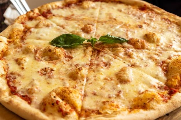 Pizza margherita con mozzarella e foglie di basilico su stend in legno.