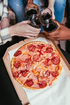 Pizza party glass soda cheer persone irriconoscibili amici interrazziali fun company tempo libero amicizia mangiare malsano concept