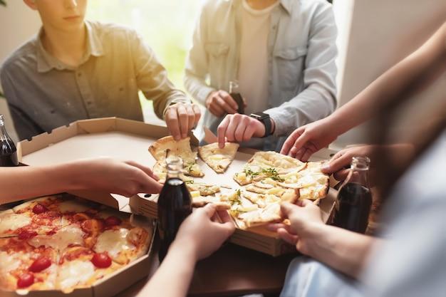 Pizza party gruppo di amici che chiacchierano mangiando pizza bevendo acqua gassata dolce