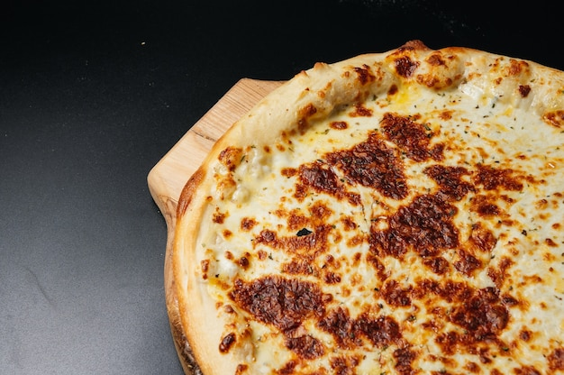 Pizza quattro formaggi su sfondo nero