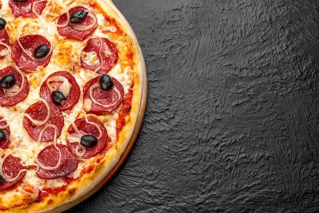 Pizza salami su fondo nero, a base di pomodoro con mozzarella, salame, cipolle e olive su supporto in legno