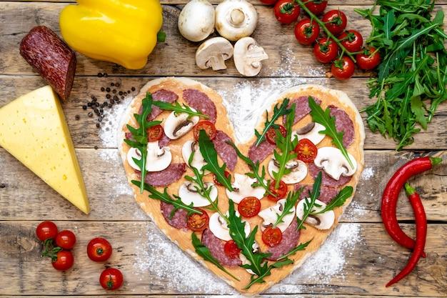 Pizza a forma di cuore e ingredienti per san valentino, processo di cottura