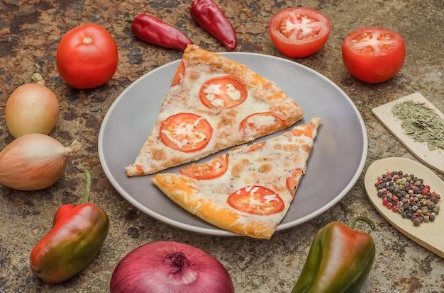 Fette di pizza con formaggio e pomodori su un piatto con ingredienti su uno sfondo arrugginito.