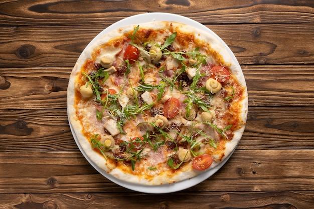 Pizza su pasta sottile con pancetta, petto di pollo, funghi marinati, rucola, pomodorini e mozzarella
