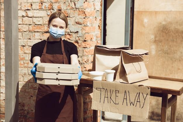 Tempo della pizza. donna che prepara bevande e pasti, indossando guanti e maschera protettiva. servizio di consegna senza contatto durante la pandemia di coronavirus in quarantena. porta via il concetto. tazze riciclabili, confezioni.