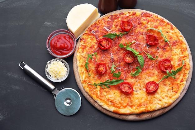 Pizza con rucola e pomodorini su tavola di legno