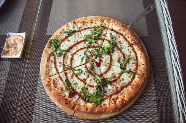 Pizza con rucola su un piatto di legno su sfondo grigio in terrazza estiva.