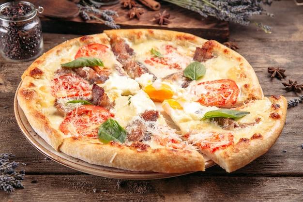 Pizza con pancetta e pomodoro sulla tavola di legno
