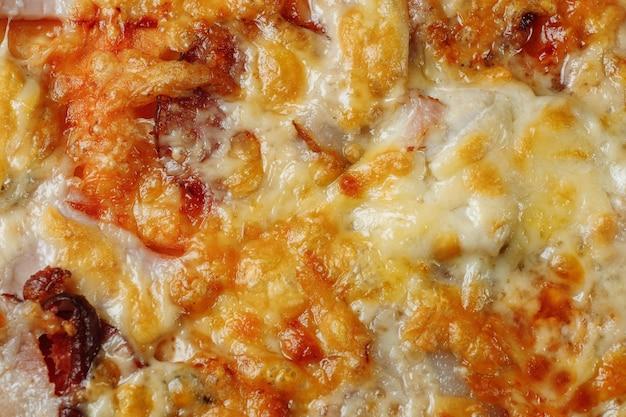 Pizza con formaggio, prosciutto e pancetta closeup