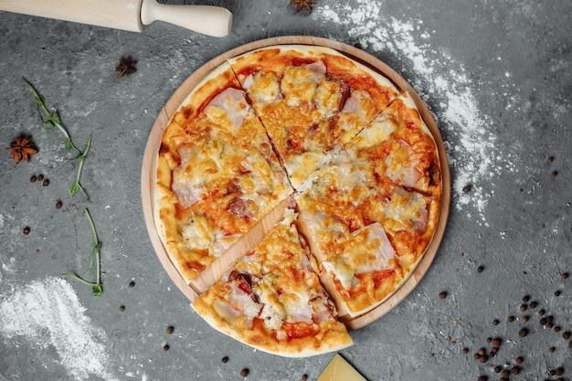 Pizza con formaggio, prosciutto e pancetta