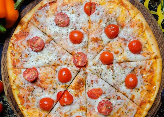 Pizza con formaggio e pomodori. cibo spazzatura, mangiare troppo e mangiare velocemente. pasto famoso italiano