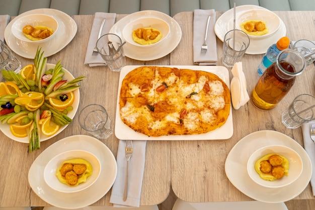 Pizza con formaggio e pomodori e piatti con purè di patate e polpette