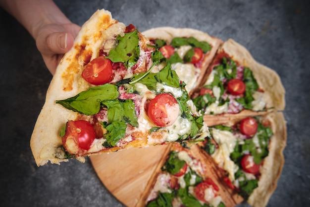 Pizza con formaggio, pomodori, spinaci e salsiccia affumicata