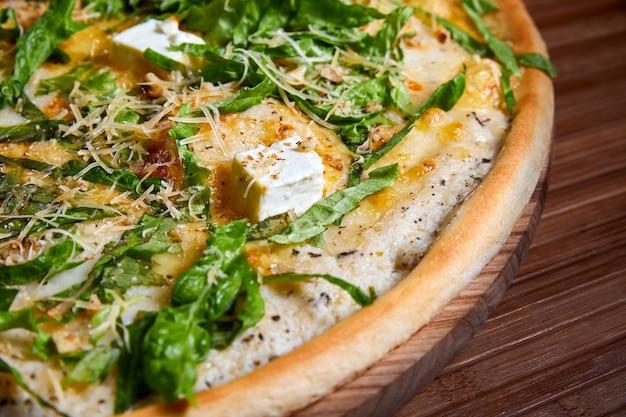 Pizza con formaggi ed erbe aromatiche su un piatto di legno