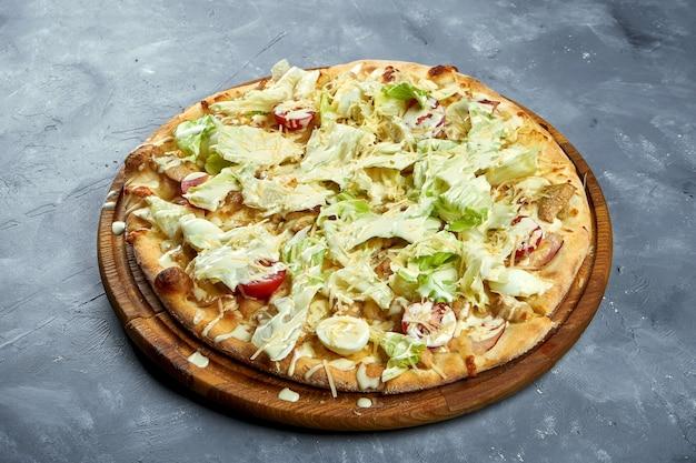Pizza con pomodorini, lattuga, parmigiano e pollo su uno sfondo grigio