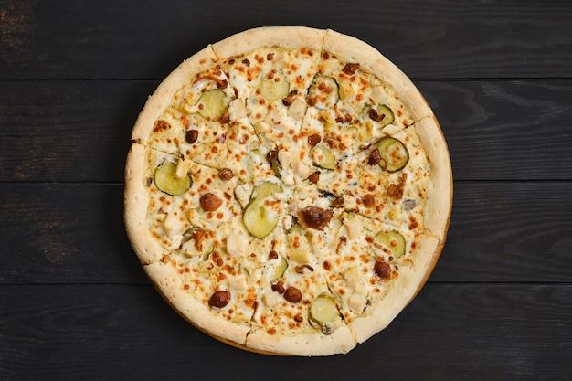 Pizza con pollo, funghi di miele e cetriolo sottaceto sul tavolo di legno scuro