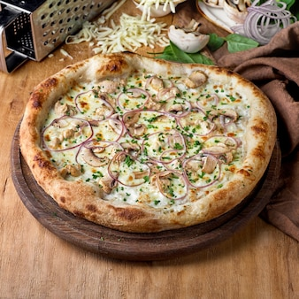 Pizza con carne di pollo funghi formaggio salsa di cipolla su fondo di legno