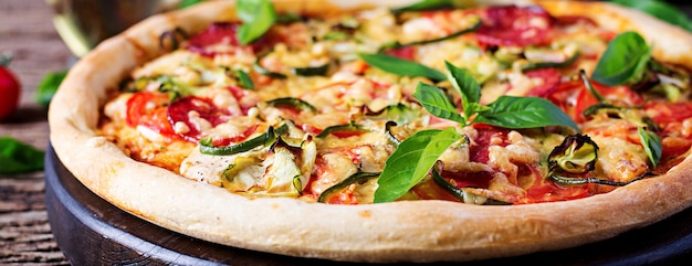 Pizza con pollo, salame, zucchine, pomodori ed erbe sul tavolo di legno d'epoca. . banner. cucina italiana