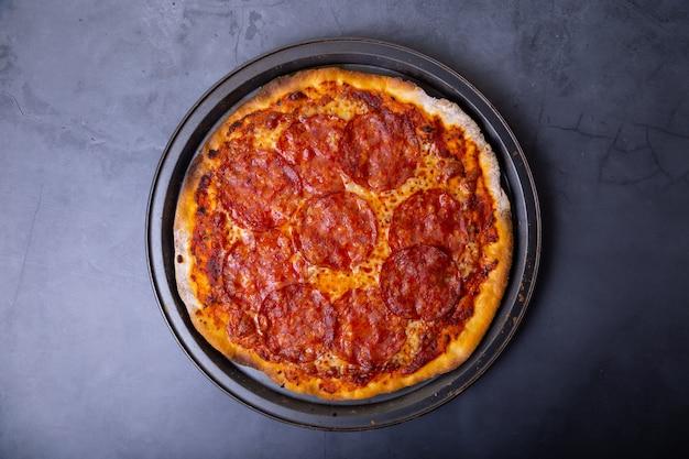 Pizza con salsiccia chorizo su sfondo nero. pizza intera primo piano, vista dall'alto.