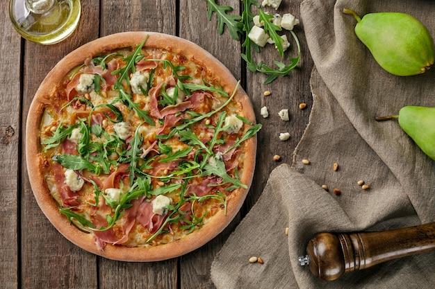 Pizza con prosciutto crudo pera gorgonzola pinoli rucola