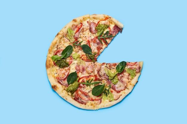 Pizza con una fetta tagliata su un blu