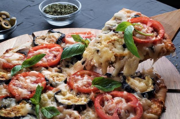 Pizza con melanzane, olive e funghi. cucina italiana. ingredienti per fare la pizza su uno sfondo nero. concetto per la pubblicità di ristoranti o pizzerie.